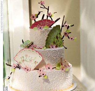 Kimberly and Jason's three-tiered confection featured traditional white cake with buttercream and fresh strawberry and Bavarian cream filling; and chocolate with strawberry and raspberry mousse filling. The pale pink frosted cake was decorated with edible hand-painted fans, chocolate branches, and cherry blossoms with butterflies. Gold frosting acc ...