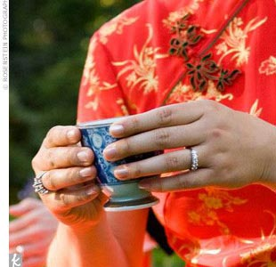 "The tea ceremony took place before dinner. Guests watched as Kimberly and Jason served tea to their parents. ""I received a gift of a gold necklace and earrings from my father,"" Kimberly says. During this time, Kimberly wore the traditional Chinese red qipao dress, which was embroidered with gold flowers."