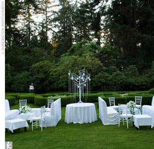 For the cocktail hour, which kept guests occupied as Kimberly changed into her final dress of the evening, the couple had a lounge area set up on the lawn near a shady tree. Sofas and white chairs were draped with white- and silver-striped velvet and arranged around low, white coffee tables decorated with silver bowls filled with white roses and li ...