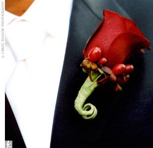 Simon and his groomsmen wore single red roses for their boutonnieres. The boutonnieres matched the bridal bouquet, which was made up of black magic roses.