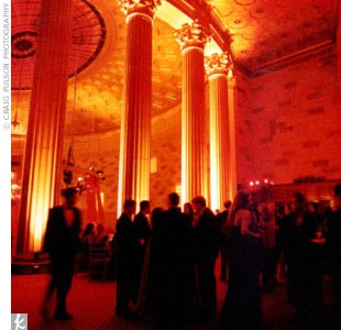 Susan and Simon created an intimate glow for their reception: Dome lighting projected red and gold throughout the room and the hall and stairways of Gotham Hall were illuminated with burgundy pillar candles in various heights, which also set the tables aglow.