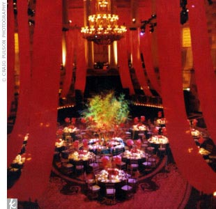 Instead of placing a dance floor in the center of the room, Susan and Simon decided to create a pond as the focal point. The pond was decorated with nine-foot-tall bamboo stalks, floating orchids, and red lanterns.