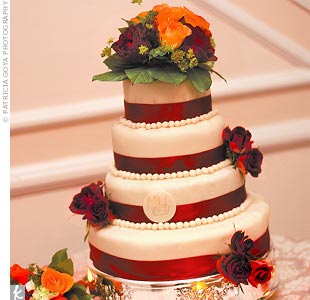 The four-tiered wedding cake had two layers of cheese cake and two of carrot cake. Each tier was topped with a white chocolate mousse fondant-like icing and dressed with burgundy silk ribbon around the base.