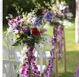 The ceremony aisle was framed with four bamboo stanchions on each side decorated with bouquets of iris, lilies, orchids, roses, carnations, and greenery. Leis of dendrobium orchids and ti leaves were strung between each stanchion.