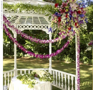 Jenn and Ken took their vows in a 1970s-style white lattice gazebo, surrounded by lush greens from the garden sanctuary. The white gazebo was accented with a large bouquet of iris, lilies, and other fragrant flowers, as well as strands of dendrobium orchid leis.