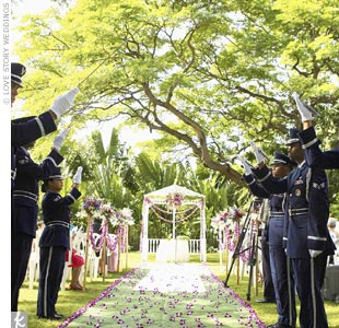 "Jenn and Ken chose to incorporate the ""arch of sabers"" tradition into their nondenominational outdoor ceremony. Honor Guard volunteers from Hickam Air Force Base stood at the top of the aisle, drawing their swords when Jenn and her father began their walk toward the gazebo. Once the couple walked back up the aisle, the volunteers again drew their s ..."