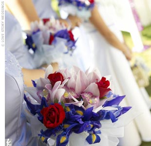 "Jenn knew when designing her bridesmaid bouquets that she didn't want her maids holding smaller versions of her bouquet. Instead, Jenn's florist created an arrangement of pink orchids, red roses, and purple and blue irises -- to match the cornflower blue bridesmaid dresses and tie in with Jenn's red bridal bouquet. ""The bouquets incorporated the we ..."