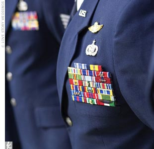 The groomsmen, who were also active duty military, wore their U.S. Air Force service dress uniforms. The groom also wore his U.S. Air Force service dress uniform and his military ribbons and pins. As military protocol instructs, there were no flowers adorning the groom or his attendants. The ring bearer and father of the bride were the only men wea ...
