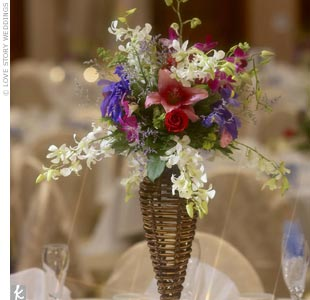For the three parent tables, the bouquets that had decorated the aisle were brought from the ceremony and placed in a rattan-and-iron candleholder. The other guest tables were decorated with floral centerpieces in a lauhala box, surrounded by clear and blue glass beads and candles, as well as a personalized bottle of wine in a lauhala wine bag.