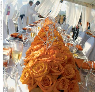 In the main tent, the only flowers used were orange pave roses in square troughs with white branches springing out, giving the space a modern, ethereal vibe.