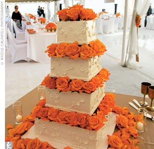 Pastry chef Amy toyed with the idea of making her own wedding cake but decided to turn the reins over to someone else once she was consumed with wedding planning. It turned out to be the right decision, as the couple was delighted with their triple berry, vanilla buttercream cake with six stacked, square tiers divided by fresh orange pave roses.