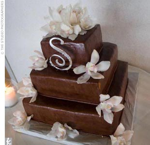 To tie in with the brown and beige color scheme, the couple steered clear of a white cake, and opted instead for a square, three-tiered confection iced in chocolate buttercream. Each layer was a different flavor, including chocolate cake with peanut butter mousse, yellow cake with chocolate mousse, and white cake with cannoli filling. The cake was  ...