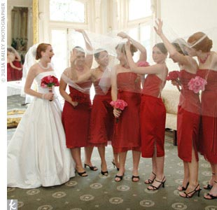 "Joellynn chose claret, tea-length gowns from Dessy by After Six for her six bridesmaids, but let each woman pick her own style. ""Not surprisingly, they each picked a different dress that fit them perfectly,"" the bride says."