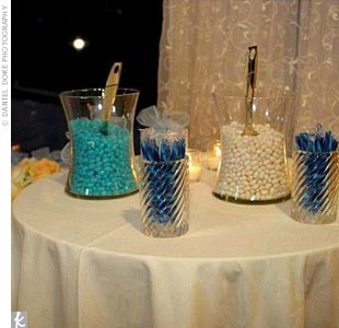 In addition to the favors at guests' place settings, Shayna and Marc also had a candy bar on offer so that guests could pick up an additional sweet treat. Shayna collected various vases and oversized martini glasses, and filled each with a different candy in the wedding colors, including blueberry and vanilla jellybeans, ice blue and white M&M's, b ...