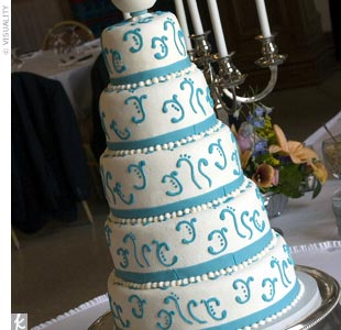 Kelli and Tre's five-tiered white wedding cake with turquoise accents beautifully complemented the wedding color scheme.