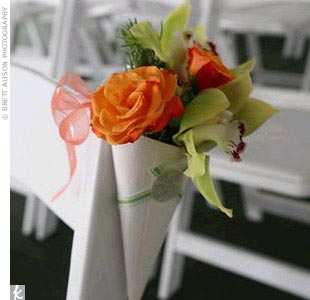 Orange roses with green cymbidium orchids placed in white cones adorned ceremony chairs, adding to the romance and elegance of the site.