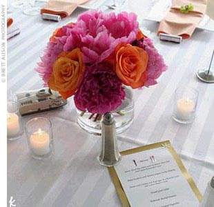 The centerpieces at each table were low, blossoming clusters of peonies and roses in pink and orange. Simple votive candles surrounded each centerpiece.