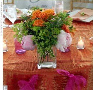 The newlyweds sat at a sweetheart table, which was set up in front of the cake table. Rebecca and Daniel's table donned beautiful blooms, votive candles, an orange crush tablecloth, and the couple's first initials hanging from ribbon.