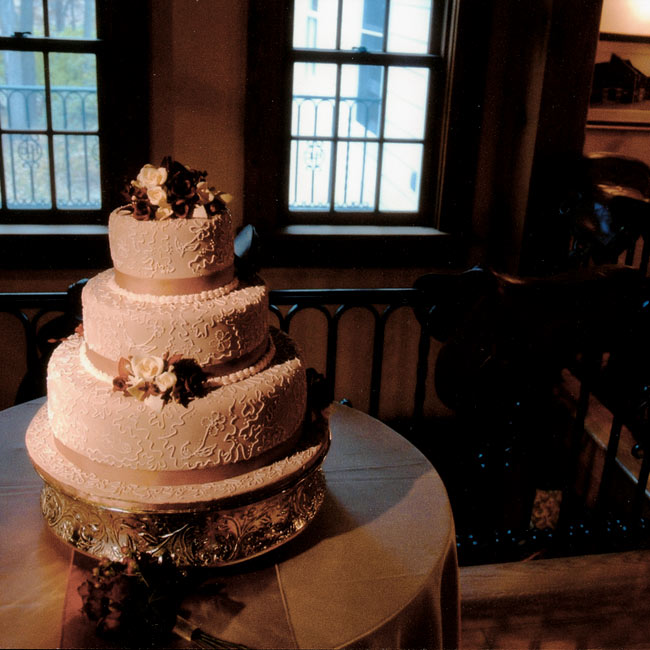 Bridget and Frank's Hungarian rum-flavored torte featured chocolate fondant with a white lace pattern to match Bridget's gown. A chocolate-hued ribbon ran along the bottom of each tier, and the torte topper was a mixture of chocolate and white candy flowers.
