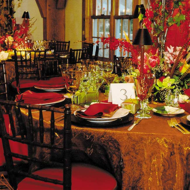 The reception hall glowed with warm arrangements of roses, greenery, and orchids.