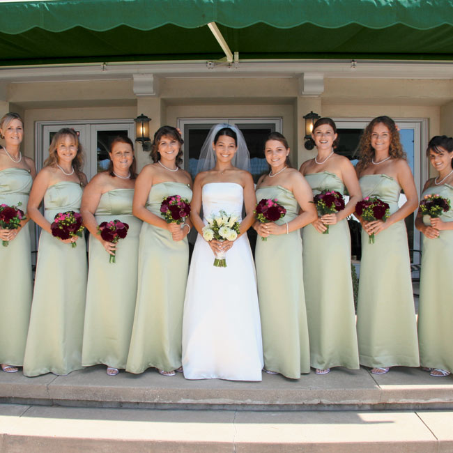 """Lisa's bridesmaids wore strapless, matte satin, A-line dresses with banded trim from The Dessy Collection by After Six. """"We chose a light green color to complement the outdoor garden feel of the wedding and the green and white house,"""" says Lisa. """"It kept everything looking fresh and cool."""""""