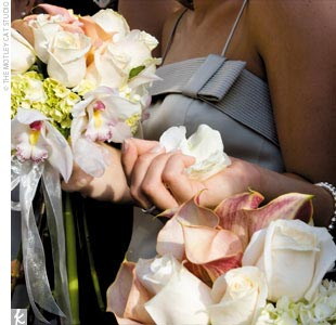 The bridesmaids carried bouquets in shades of apricot, ivory, and rose.