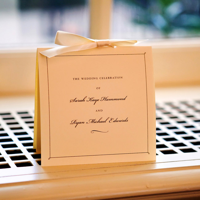 Sarah and Ryan's Crane & Co. invitations announced their wedding's simple, elegant style: a thermographed combination of serif and script on square ecru card stock, presented in gold-lined envelopes. The wedding programs and menus repeated the simple but striking design theme.