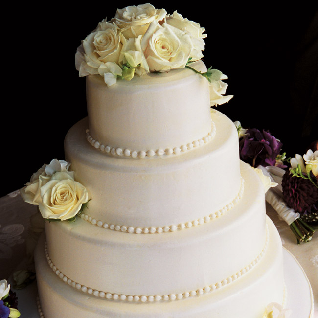Brandi and Jeff served a four-tier round stacked cake with white buttercream frosting. The flavors were white chiffon cake with raspberry cordial and white-chocolate mousse filling and red velvet cake with cream cheese filling. It was decorated with flowers that matched the centerpieces.