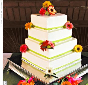 Each layer of the four-tiered cake was lined with green ribbon and adorned with fresh gerbera daisies. Half the cake was dark chocolate filled with Baileys Irish Cream mousse, while the other half was white cake filled with fresh strawberries. It was topped with fresh buttercream icing.
