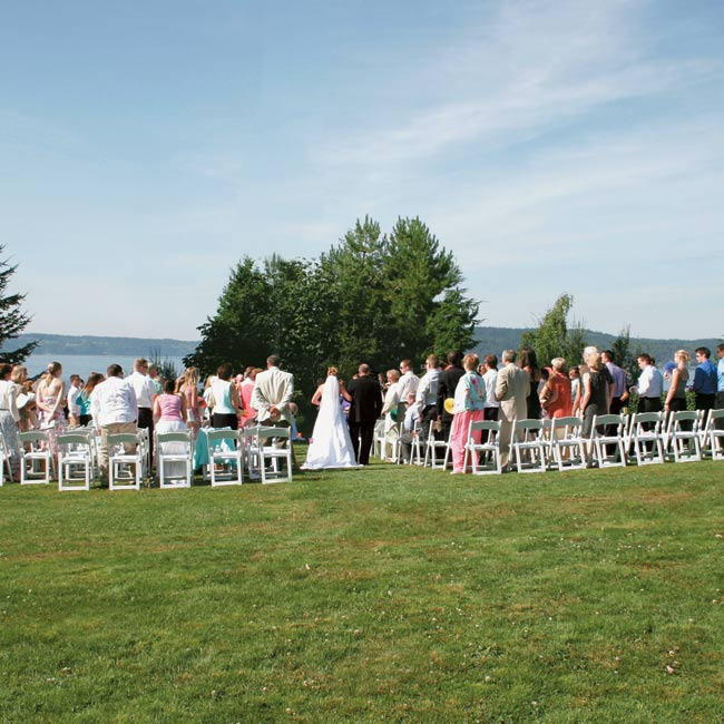 Brittany and Steve recited their vows on the lower lawn at Point Defiance Park, overlooking Puget Sound. The aisle was lined with pink, green, orange, and yellow glass flower votives, and guests sat on white garden chairs facing the water. A small table with a white linen tablecloth and a hurricane vase with a candle inside denoted the altar.