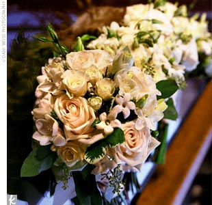 Dori carried a bouquet of hand-tied cream roses and freesia with contrasting bright green hypericum berries.
