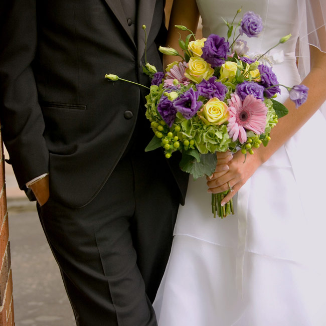 """Flowers were my biggest splurge and what I was most excited to see,"" says Tiffany. Her bouquet was full of hydrangeas, gerbera daisies, lisianthus, green berries, and jade roses, all tightly wrapped with a sheer green ribbon. The bridesmaids carried smaller versions of the bridal bouquet."