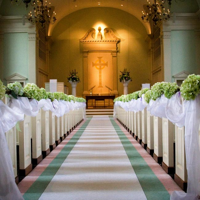 The pews were connected with fabric and each one decorated with green hydrangeas and a green and purple ribbon.