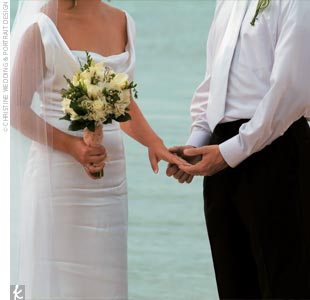 The bride carried a bouquet of white hydrangeas, roses, freesia, and mini calla lilies, while the bridesmaids carried similar bouquets with pink and green floral accents.