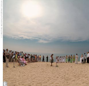 "Ashley and Clint married on a secluded beach on Lake Michigan (part of the Sleeping Bear Dunes National Lakeshore) near Glen Arbor. White heart-shaped signs with pink tissue flowers directed guests down a path through dune grass to the ceremony site. ""The water was surreal -- no waves, and the voices from the beach seemed to carry for miles.  Every ..."