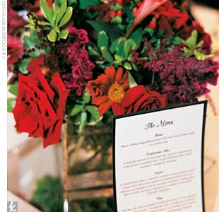 "Striking red flower arrangements in square vases graced every table, alongside charming photos of the bride and groom from the time they were 1 year old: ""Table three had a picture of Andrew at age three and a picture of me at age three, and so on,"" Erica explains."