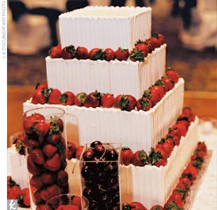 Erica and Andrew designed their own cake, inspired by a combination of pictures they had seen. The four-tiered square cake featured fresh strawberries and three different fillings, and was presented alongside vases of red berries.