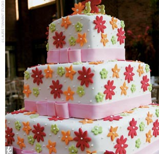 A three-tiered square cake was decorated in orange, green, and red fondant flowers with pink ribbons of icing. Inside, a carrot cake that was filled with pineapple, dried raisins, and cherries, and finished with cream cheese frosting satisfied everyone's sweet tooth.
