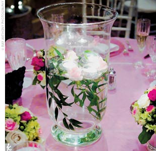 The rose and green–themed reception decorations included glowing hurricane lanterns, floating votives, and julep cups filled with tiny flower arrangements.
