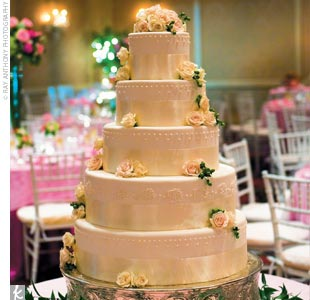 "The monogrammed five-tiered cake continued the airy, summery theme with fresh flowers, hypericum berries, and pearlized Swiss dots. ""It was so delish that we actually ran out of cake!"" says the bride. Maybe that's because of the confection's unique combination of flavors: banana nut with vanilla buttercream, chocolate with vanilla buttercream, and  ..."