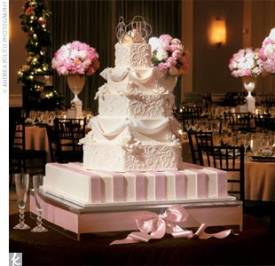Another highlight of the evening was the bride's opulent cake, a six-layered confection that alternated round with hexagonal tiers. The white-on-white icing was fashioned in a lace pattern from the bride's veil, and each layer was accented with Swarovski crystals. Pink ribbon details graced the bottom layer, and the top held a handmade, four-sided  ...