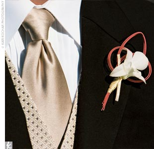 Ethan wore a boutonniere of white dendrobium orchids tied with silk ribbon. The orchids were then pinned to the knot of a Mizuhiki cord, which is a Japanese cord used to make special knots believed to bring the recipient good luck.