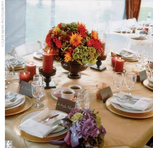 For centerpieces, urns overflowed with orange roses, and dark green and purple hydrangeas were flanked by hurricane lanterns holding tangerine candles. Gold chargers with white china graced each place setting.