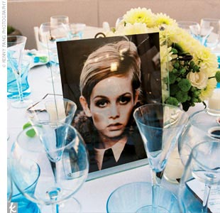 Low centerpieces of white and green dahlias with green berries and fiddleheads rested inside clear cylinder vases, which were positioned next to framed photos of iconic '60s celebs the likes of Twiggy, Sean Connery as James Bond, Audrey Hepburn, and Andy Warhol.