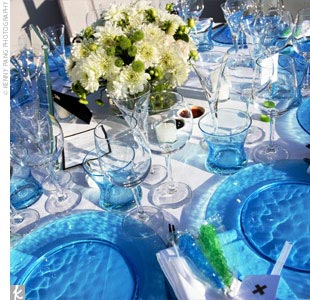 Reception tables were draped in crisp white linens and set with turquoise chargers topped with white square plates.