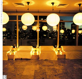 After the ceremony, guests were transported even further back to the '60s as they made their way out onto the venue's terrace. Round white paper lanterns inside and candles placed in long cylindrical vases outside provided a warm glow. Circular shell curtains separated the terrace from the ceremony space, which was turned into a minimalist lounge d ...