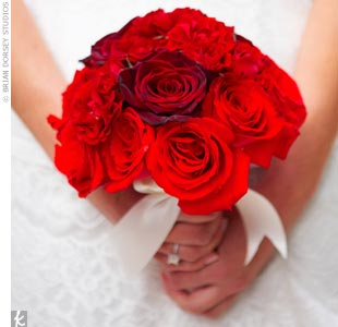 Reminiscent of Christina Aguilera's own flowers, Jessika carries a dramatic bouquet of roses in various rich red tones. The tightly bound bouquet is wrapped in white satin ribbon, which matches Jessika's gown.
