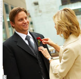 Carley helps Michael with his simple, yet striking, red rose boutonniere, chosen to match Jessika&#39;s bouquet. The groom looks handsome in a three-button jacket by Tallia that features a black faille vest and long black satin tie.