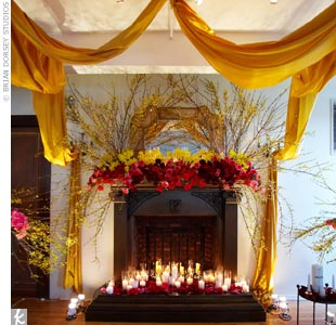 A stylish New York City loft is appointed with lush flowers in rich red and gold hues, thanks to event designer David Beahm. In addition to the flowers, a candlelit glow and carefully draped golden fabric creates a romantic scene around the altar.