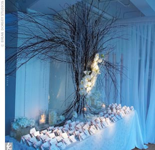 An elaborate display complete with an organically sculpted centerpiece, candles, and winter white flowers, is home to the escort cards. Each silvery card is adorned with a crystallized branch tied with a pink ribbon for an icy, wintry detail.